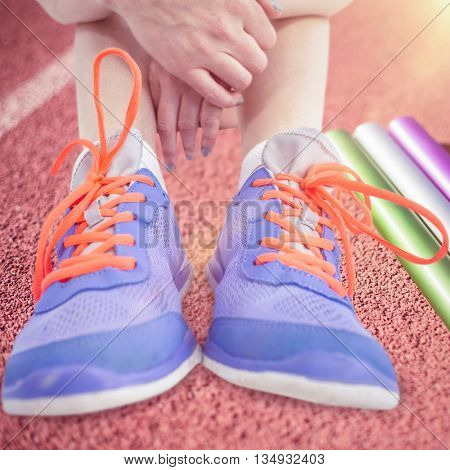 Athlete woman sitting with sports shoes against focus of relay baton on a race track