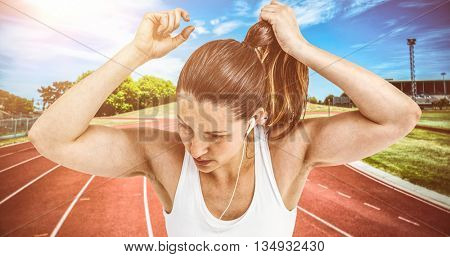 Athlete woman tying her hair and listening to music against high angle view of track