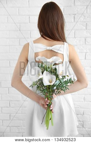 Beautiful young woman holding bouquet of callas on white brick wall background