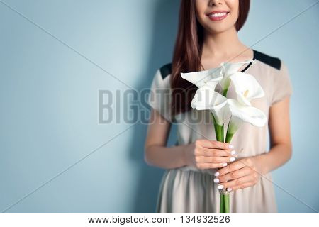Beautiful young woman holding bouquet of white callas on light background