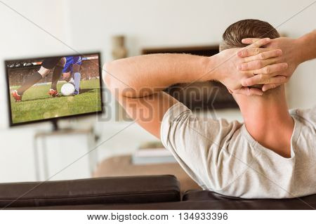 Man relaxing on his couch against football players tackling for the ball on pitch