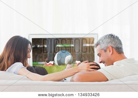 Football player kicking ball against family watching television together sitting on sofa