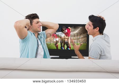 Disappointed soccer fans watching tv against rugby players tackling during game