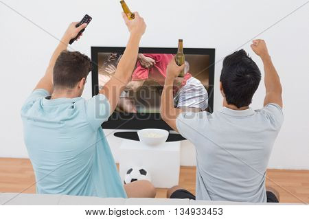 Excited soccer fans watching tv against rugby players doing a scrum