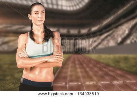 Sporty woman posing with her arms crossed against view of a running track
