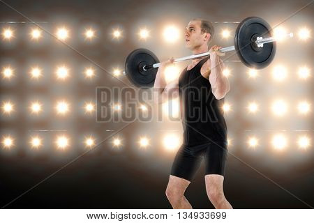 Bodybuilder lifting heavy barbell weights against composite image of orange spotlight