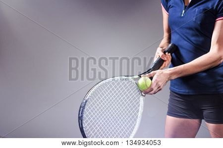 Tennis player holding a racquet ready to serve against grey background