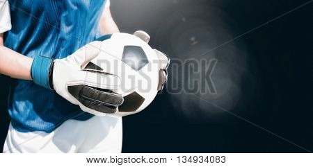 Close up of a football held by sportswoman against view of lighting