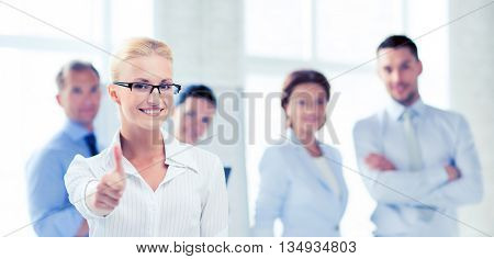 attractive businesswoman in office showign thumbs up