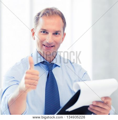 handsome businessman with papers showing thumbs up