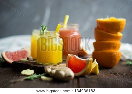Fresh grapefruit and orange juice on a wooden rustic background