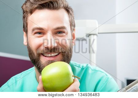 Portrait of young handsome male doctor with beard smiling with perfect straight white teeth holding green fresh ripe apple. Face expressions emotion healthcare medicine.