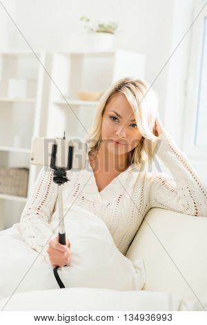 Attractive grimacing girl taking selfie holding a selfie stick.