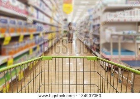 shopping cart view with Blurred defocused background of generic supermarket people walking shopping