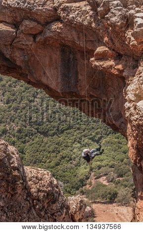 KESHET (ARCH) CAVE, UPPER GALILEE, ISRAEL - MAY 12, 2016: Man rappelling down from the arch, suspended in the air.