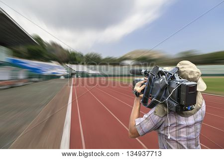 Video cameraman operator with motion blur sport stadium running track lines