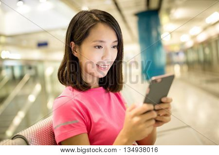Woman use of mobile phone in train platform