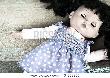 Concept Abandoned PersonAbandoned doll laying on old wooden vintage