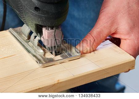 Closeup photo of jigsaw sawing wooden piece.