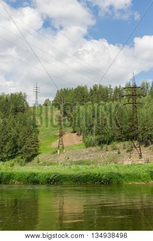 rusty high voltage power line leading through the river