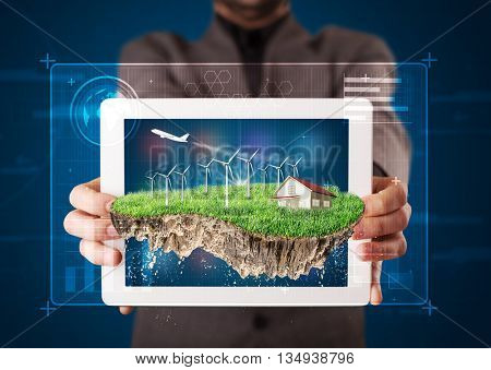 Young businessman presenting a perfect ecology land with a house and windmills