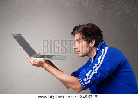 Attractive young man holding modern notebook