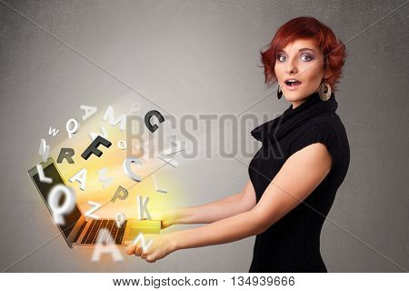 Pretty young woman hoolding notebook with colorful abstract letters