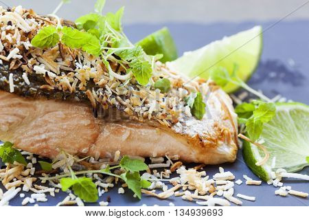 Salmon grilled with lime and toasted coconut.  Garnished with micro herbs.