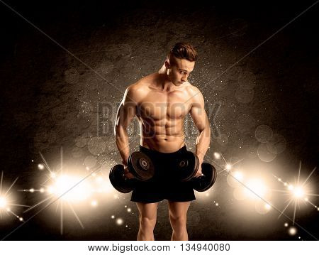 An attractive muscular guy working out with weights and showing naked upper body with illustrated lights and bokeh concept