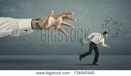 Businessman with question marks running away from a big hand concept on background