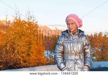Girl teenager in silver down jacket in autumn tundra in the Arctic Circle.
