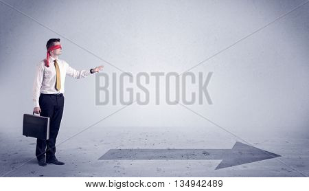 A confused blind salesman standing in front of a drawn arrow on the floor pointing in the right direction concept.