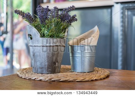 Faked flowers in wooden bucket and napkin paper in bucket.