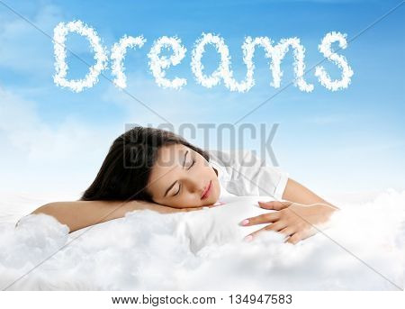 Beautiful girl lying on blue cloudy sky and text Dreams