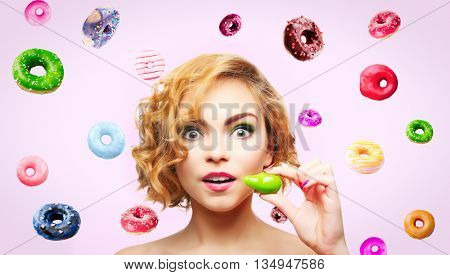 Beautiful girl with colorful donuts on light background