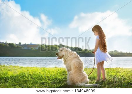 Little girl and big kind dog on the riverside