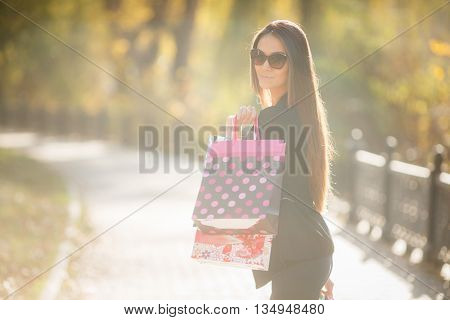 Beautiful slender young brunette woman with long straight hair,wearing a black light jacket and dark blue jeans,wears dark sun glasses,posing in yellow autumn Park,holding hands of colorful paper shopping bags