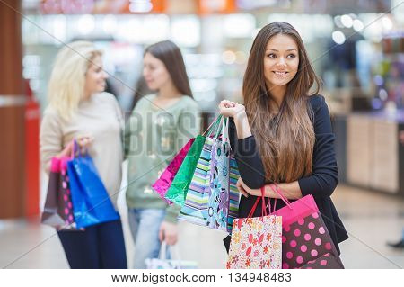 Beautiful slender young brunette woman with long straight hair and brown eyes,wearing a black light jacket,posing in a supermarket on the background of the two friends,in the hands holding colorful paper shopping bags