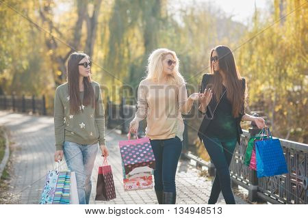 Three happy women-girlfriends,two brunettes with long straight hair and one blonde,wearing sun glasses,dressed in jeans and a light sweater,holding colorful paper shopping bags,walking in yellow autumn Park after shopping