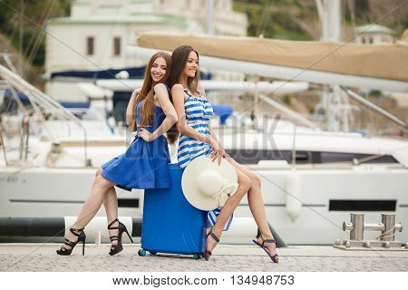 Two young beautiful woman brunette with long straight hair,cute smile,dressed in tunics of blue and blue-white stripe,in hand at one of the bridesmaids-a large white straw hat ,posing at the harbour, sitting with a blue suitcase on wheels