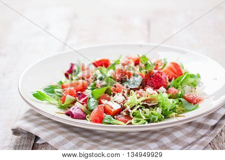 Summer salad with grapefruit strawberry mint balsamic and cheese on a plate on a wooden background closeup