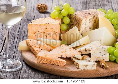 Glass of white wine and Cheese plate: organic homemade goat cheese with walnuts and spices. Green Grapes and walnuts on an old rustic background studio lights close-up
