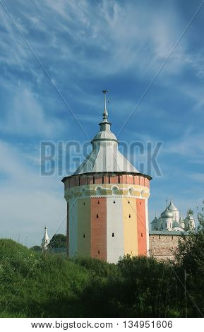 Watch tower of Spaso-Prilutsky Monastery in the Vologda city Russia. Blue sky and green grass. Castle defense wall