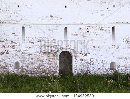Spaso-Prilutsky Monastery in the Vologda city Russia. Ancient wall and green grass. Castle defense wall