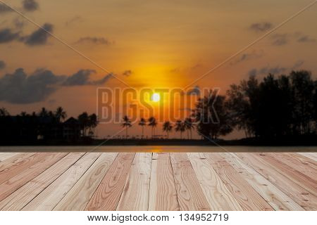 Wood floor on Blured Sunset on the beach with beautiful skySeaview background for Summer sunset mountains and sea. Sunset reflection in the seablur scenery background