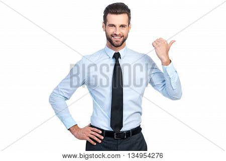 Pay attention to this! Confident young handsome man in shirt and tie pointing away and smiling while standing against white background