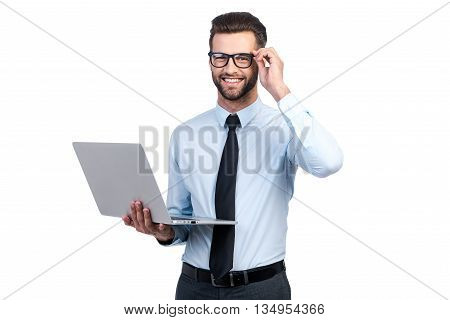 Confident business expert. Confident young handsome man in shirt and tie holding laptop and smiling while standing against white background