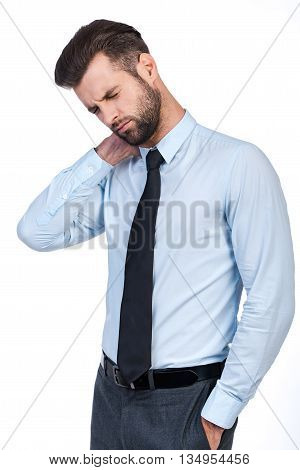 Feeling pain in neck. Frustrated young man in shirt and tie massaging his neck and keeping eyes closed while standing against white background