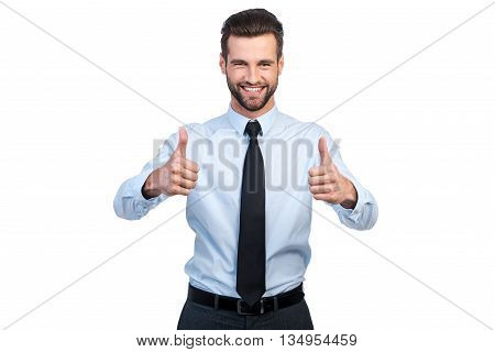 Thumbs up for success! Confident young handsome man in shirt and tie showing his thumbs up and smiling while standing against white background