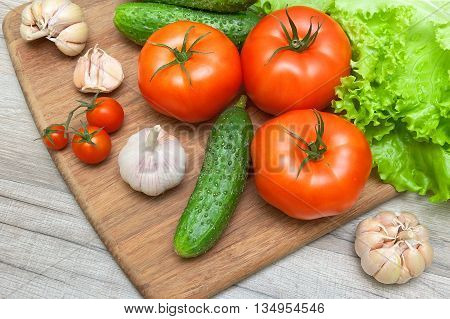 fresh vegetables on a cutting board on a wooden table. horizontal photo.